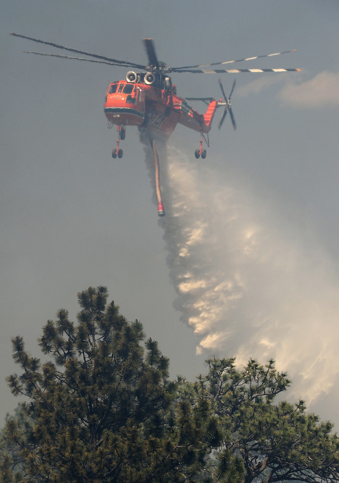 Walt Hester   Trail Gazette<br /> A type-one helicopter drops nearly 3,000 gallons of water on the Woodland Heights Fire. At least 16 structure burned in the Saturday afternoon fire.