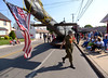 John Lang, Vietnam Veterans of America, Chapter 590, passes beneath the tail of the group's Huey helicopter as he heads for the flag raising at the Arthur V. Savage American Legion Post #100 before the start of the Wyndmoor Memorial Day Parade May 25, 2015.  Photo by Bob Raines