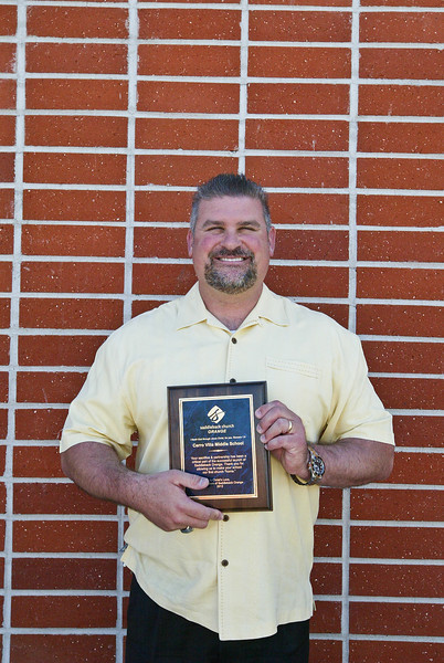 Ken Miller, the principal of Cerro Villa Middle school holding the plaque awarded to him.