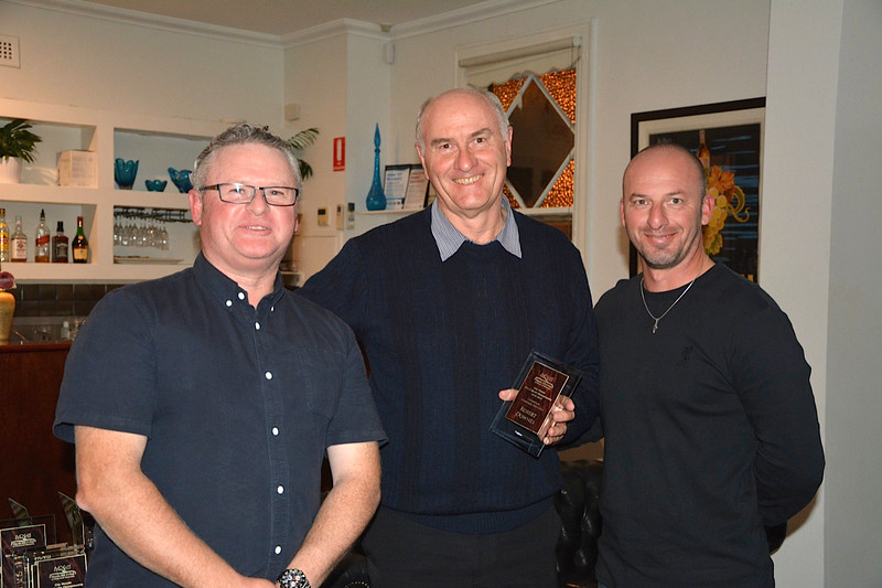 Robert Downes (centre) receives his Standard NA winner's trophy from Tim Emery (left) and Randy Stagno Navarra