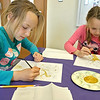 "Kids try and paint recreations of Gustav Klimts' painting ""The Tree of Life"" at the Leominster Public Library on Tuesday morning. Working hard on their painting is twins Ella and Lily Delorenzo of Leominster. SENTINEL & ENTERPRISE/JOHN LOVE"