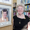 Former Mayor Mary Whitney stands by her portrait at the Fitchburg Public Library on Thursday afternoon during a gallery opening of Fitchburg's mayoral portraits. SENTINEL & ENTERPRISE / Ashley Green