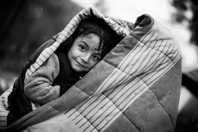 A boy hides from the  rain under a blanket with his mother in Moria registration camp. Lesvos Island, Greece, 2015 ---- Un jeune garcon se protège de la pluie sous une couverture avec sa mère dans le camp d'enregistrement de Moria. Ile de Lesbos, Grèce, 2015