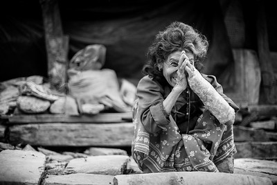 A woman, injured, is still smiling in front of the remains of her house in the Sindhupalchowk area.