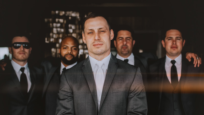 """Groom and groomsmen posing for the classic """"Guys"""" shot in matching light and dark grey suits"""