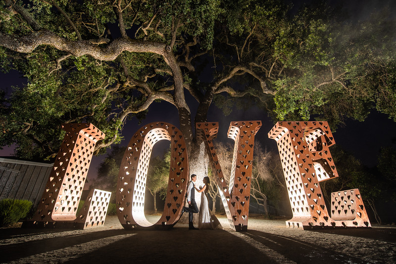 Beautiful young couple inside large Love sign at Sycamore Creek Vineyards, Girloy, Ca.