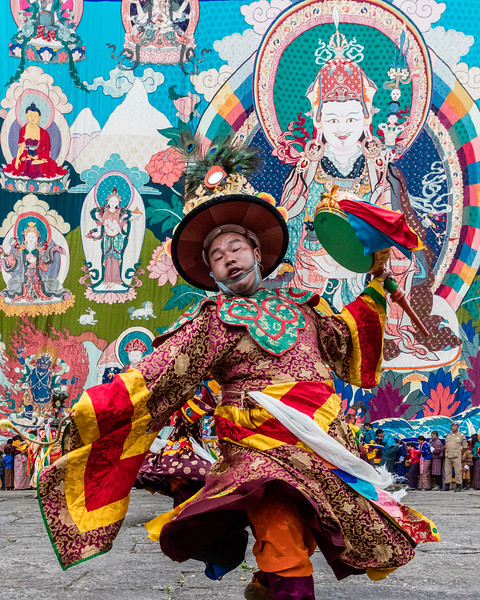 The background behind this dancer at a rural teschu festival in Bhutan is a ten story tall silk applique (throngdrel) hung especially for this festival from a temple building.  The celebrants lined up along the bottom of the throngdrel demonstrate its massive scale. [SEEK OUT FESTIVALS AND CELEBRATIONS section, third paragraph, page 36]
