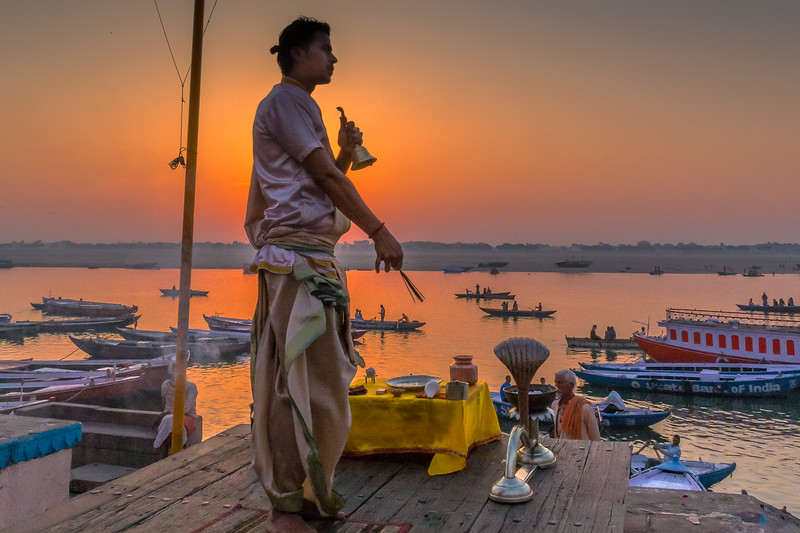 A sadhu (holy man) starts the day with a ceremony on the ghats as the sun rises over the Ganges River in Varanasi. With the sun blocked by the main subject, you can take better advantage of the sunrise colors in th sky. [Pages 34-35]