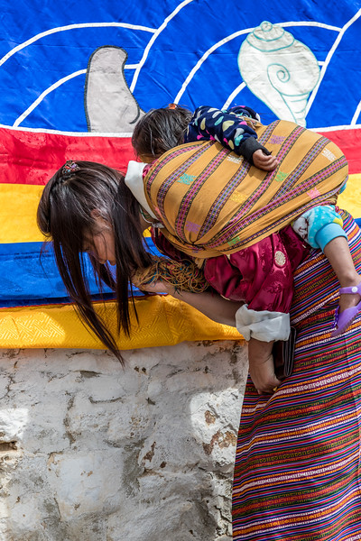 Kurjey Tshechu, Bumthang, Bhutan. A mother with her child approaches the thongdrel with reverance.