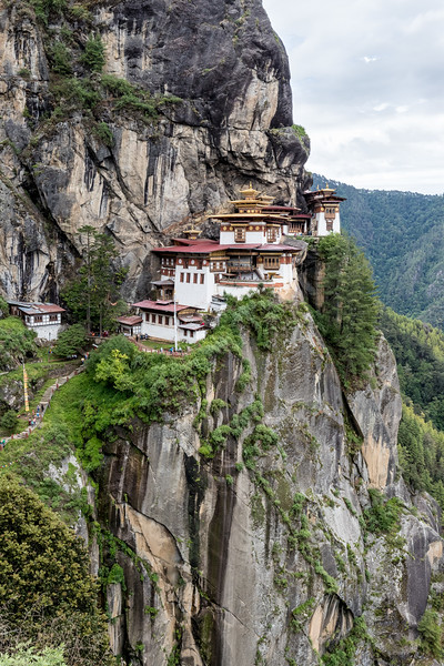 Taktsang, Bhutan. The monastery complex is built into and supported by an indentation in a massive vertical cliff. The Paro valley floor is 900m below. For scale, check the people on the stairs going up to the building; they're at the mid-left edge of the image.