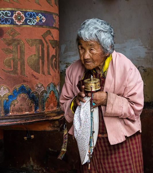 Jakar, Bhutan. A devout elderly woman after spinning a large temple prayer wheel. She carries a small one, as well.