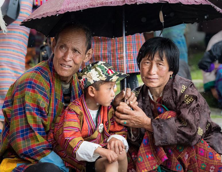 Kurjey Tshechu, Bumthang, Bhutan. Tshechu attendees shield themselves from the rain.