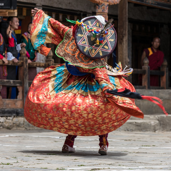 Nimalung Tshechu, Bumthang, Bhutan. A black hat dancer performs in the courtyard of the monastery. Elaborately decorated black hats are a key custume element of the Dance of the Black Hats (Shanag).