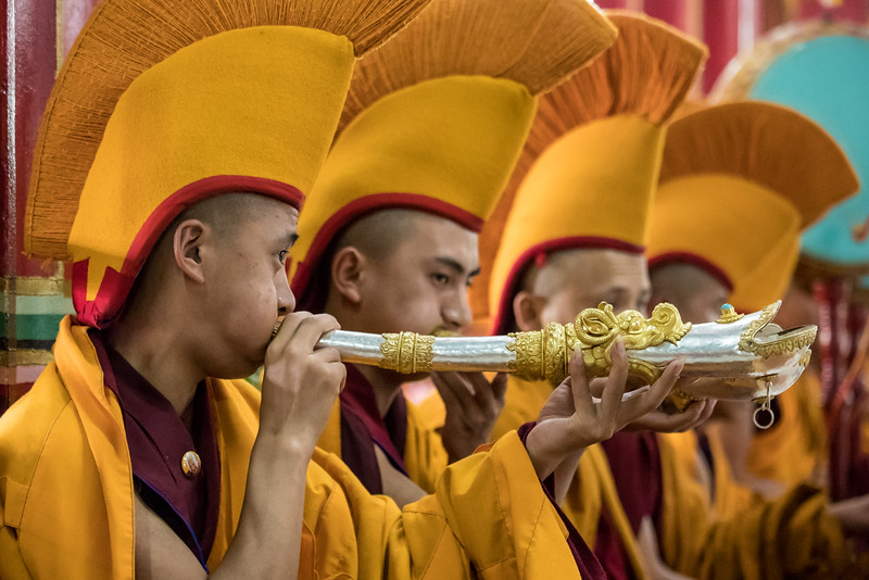 Lhodrak Kharchu Monastery, Bhutan. Monks wearing special ceremonial hats provide horn accompaniment for a prayer service.