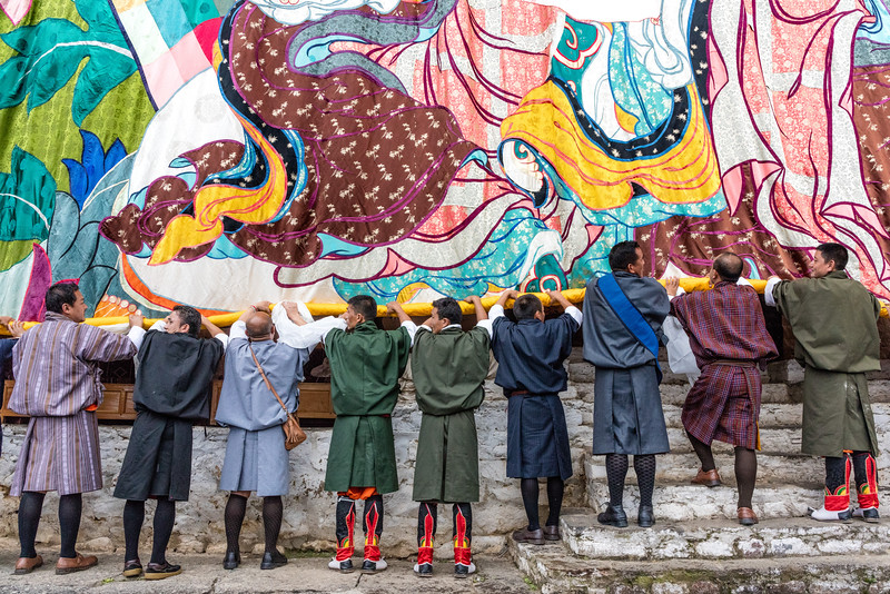 Kurjey Tshechu, Bumthang, Bhutan. Taking down the thongdrel by rolling it from the bottom. Eventually, these workers carry the fully rolled thongdrel on their shoulders off to storage.
