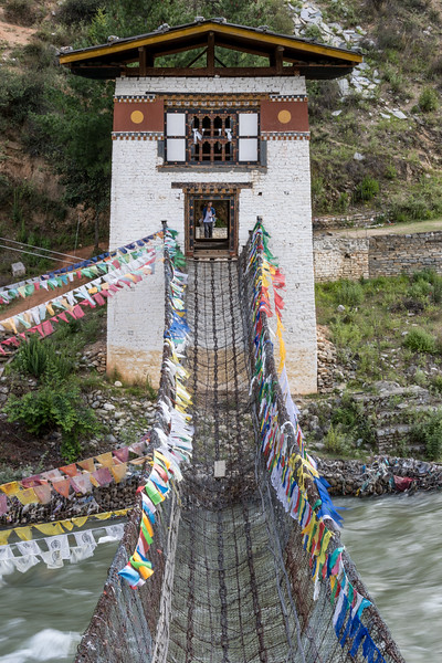 Paro area, Bhutan.  A bridge across the Paro Chu (river) provides access to a farm. The bridge is supported by several parallel chains consisting of massive metal links. Modern chain link mesh overlays those chains.