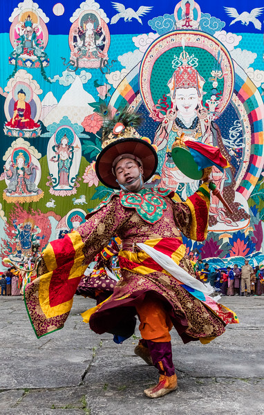 Kurjey Tshechu, Bumthang, Bhutan. A black hat dancer, with the massive thongdrel in the background. Note the tshechu attendees lined up for a blessing ceremony along the base of the thongdrel.