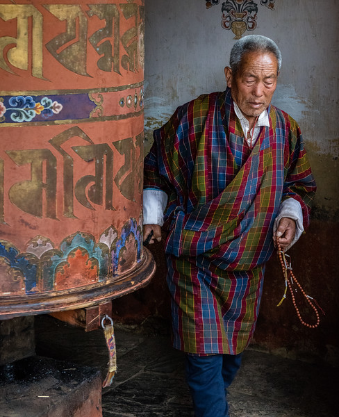 Jakar, Bhutan. An elderly man with prayer beads spins a temple prayer wheel.