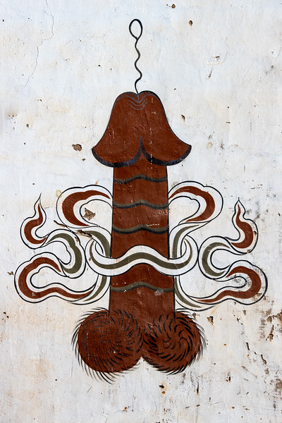 Sopsokha, Bhutan. In the village just below the temple that honors the Divine Madman, the wall of a home is decorated with a painted phallus, as he encouraged. Phallus representations are widely considered in Bhutan to help ward off evil and to bring good luck and fertility.