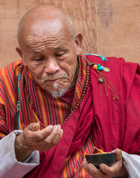 Lhodrak Kharchu Monastery, Bhutan. A prayer service participant enjoys the free food afterwards.