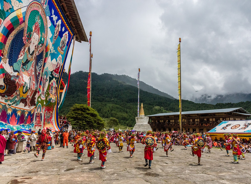 Kurjey Tshechu, Bumthang, Bhutan.  The festival dance area and the dancers are dwarfed by a massive thongdrel on the left. A thongdrel is a large applique religious image that is typically unfurled only for teschus or festivals such as this one.