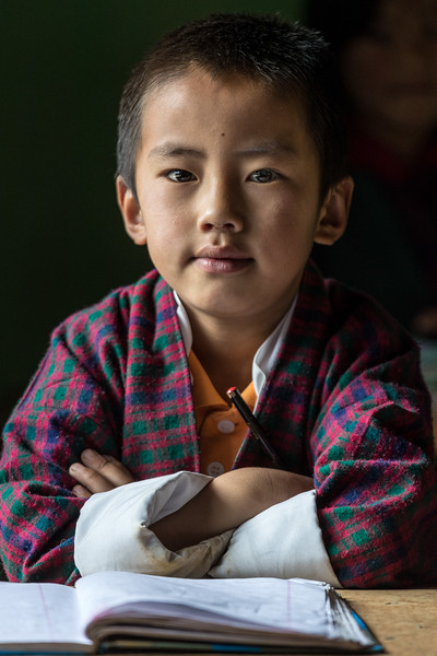 Bayta Primary School, Gangtey, Bhutan. A student pauses his work for a portrait.