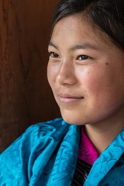 Nimalung Tshechu, Bumthang, Bhutan. A young woman observes the dancing.