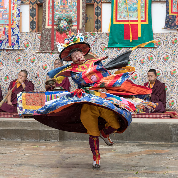Nimalung Tshechu, Bumthang, Bhutan. A black hat dancer with accompanying musicians in the background.