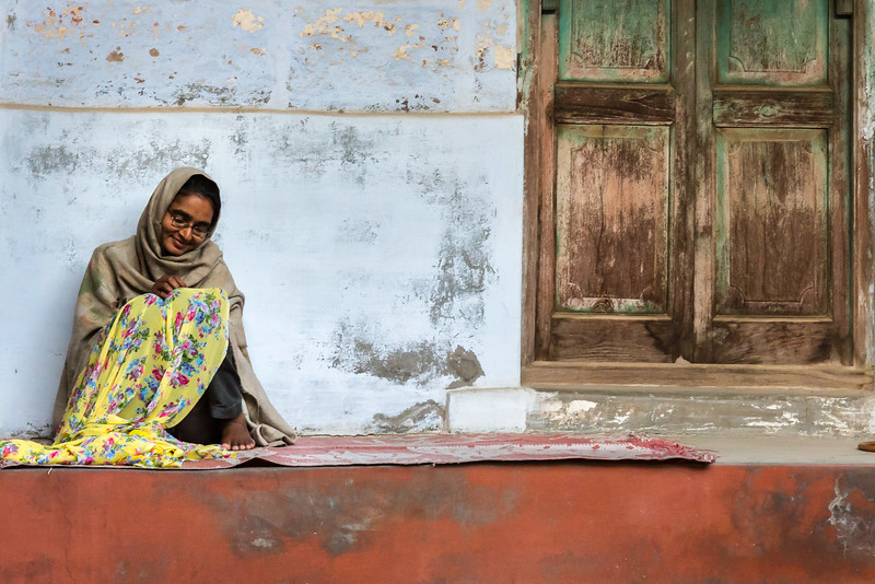 A woman sits against the blue walls of centuries-old Jodhpur, hand-stitching a sari fall. The stitches need to be invisible, and therefore tiny, so good light is essential.