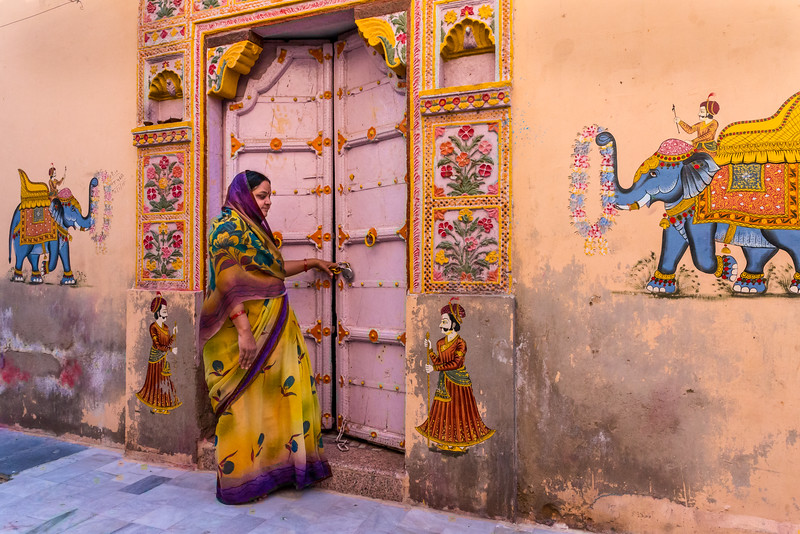 The women of India, like this one in Jodhpur, often are dramatically dressed. The walls of this Blue City enclave often are elaborately decorated, as well.