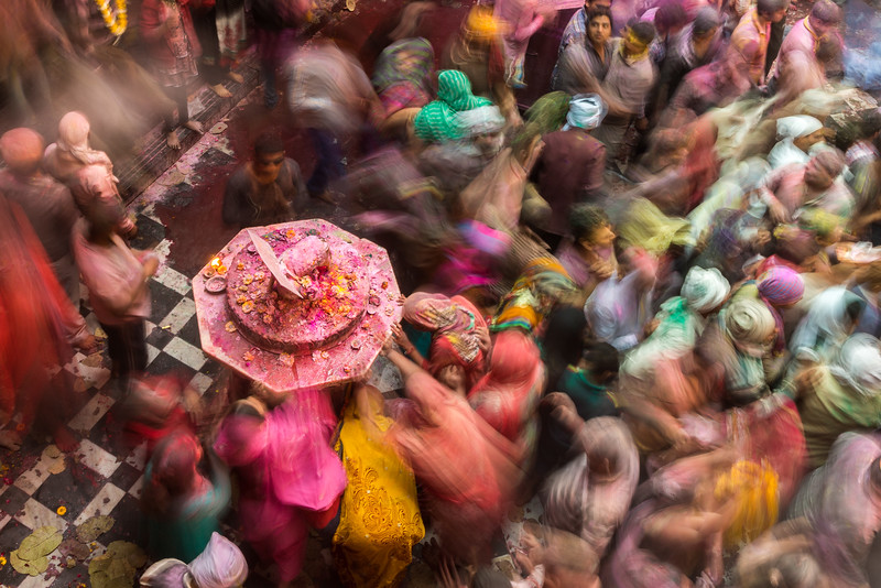This pedestal holds a small metal sculpture of a cow and calf. Cows are sacred in Hinduism and synonymous with Lord Krishna. In this extended exposure, Holi celebrants are paying respect and touching the pedestal for a blessing.