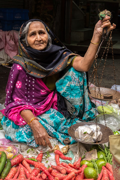 A vegetable vendor in Old Delhi, India, weighs the purchases of a customer.