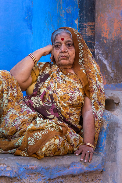 A contemplative woman against the colorful walls of Jodhpur, India.