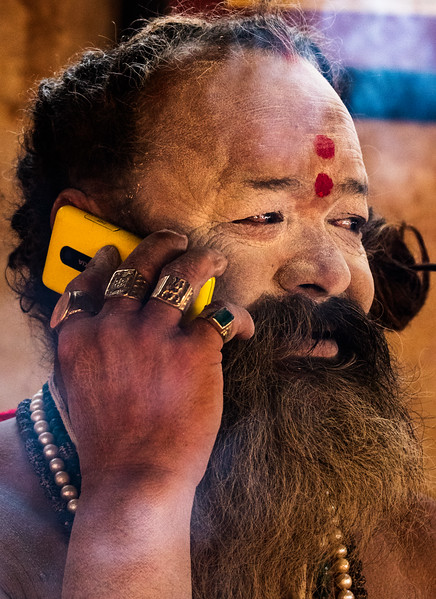 Haridwar, India. This sadhu maintains a dhuni (or sacred fire) near the ghats in Haridwar. He welcomes pilgrims and visitors to join him and his followers around the fire for chai. His traditions are ancient, his technology modern.