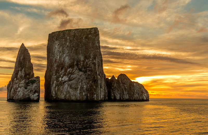 Leon Dormido, San Cristobal, Galapagos. A sunset view of the remains of a lava cone that split in two over the years. The slot between the two is wide enough for tour boats to pass through.