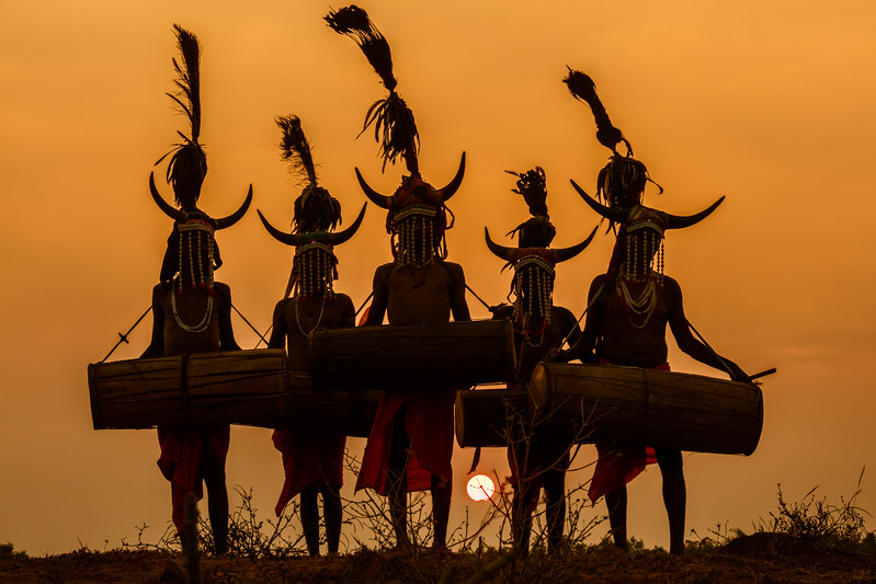 Naener, Baster, Chhattisgarh, India. Bison Horn tribal dancers against the setting sun.