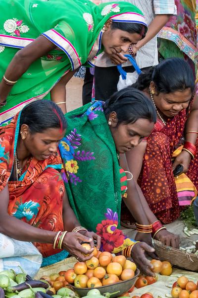 Chilpi, Bhoramdeo, Chhattisgarh, India. Women inspect market fruit.