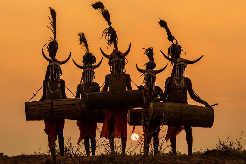 Naener, Baster, Chhattisgarh, India. Bison Horn tribal dancers against the setting sun.