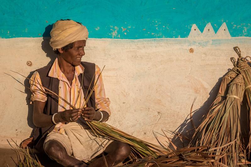 Benda, Bhoramdeo, Chhattisgarh, India. A Baiga man assembles a straw broom.