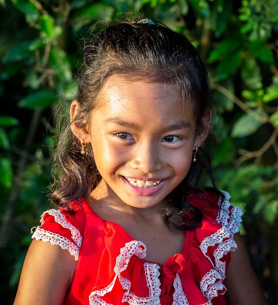 Angkor Ban Village, Cambodia. A young girl glows in the setting sun along a bank of the Mekong River.
