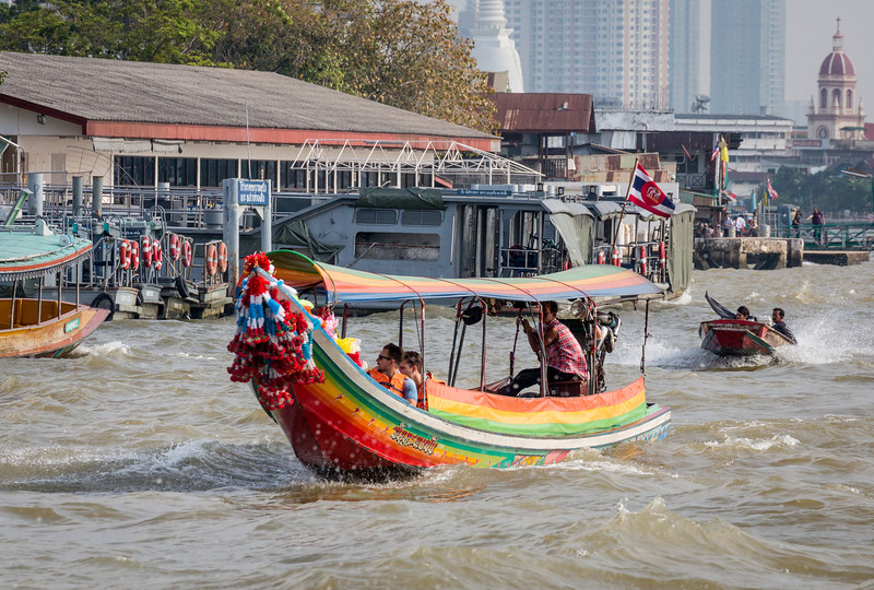 Bangkok, Thailand. The Chao Phraya River is a vibrant transportation corridor and its banks hum with activity, including, here, a base for the Royal Thai Navy, skyscrapers, a Buddhist stuppa and the Santa Cruz Catholic Church.