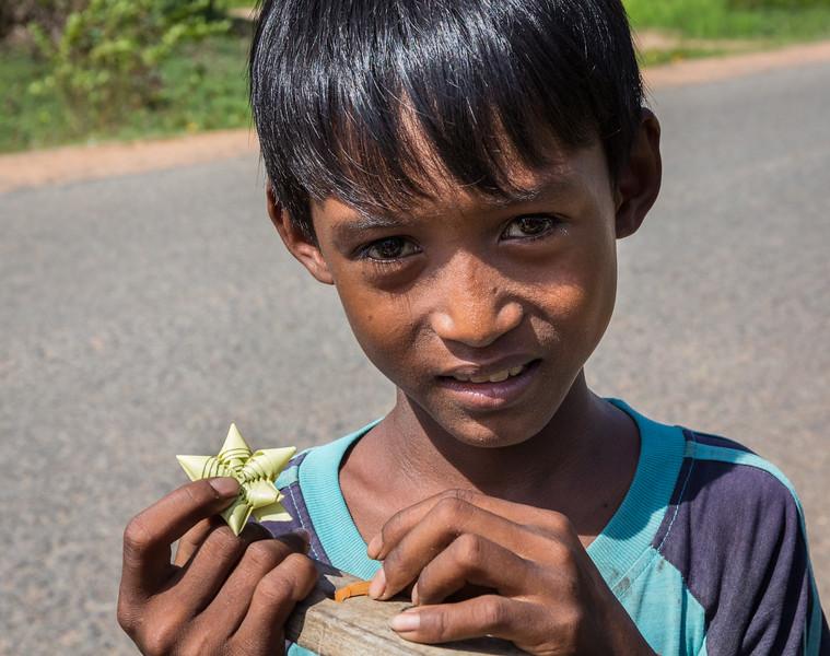 Kampong Tralach Village, Cambodia. A young boy offers a handmade souvenir gift.