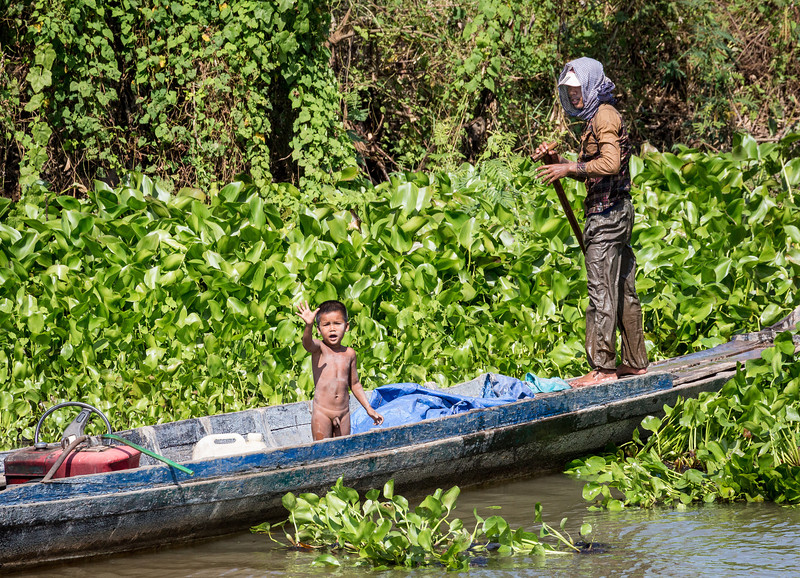 Tonle Sap River, Cambodia. A young boy waves to a passing boat.