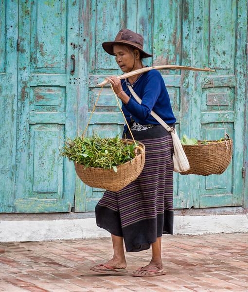 Luang Prabang, Laos. A vegetable vendor carries her produce.