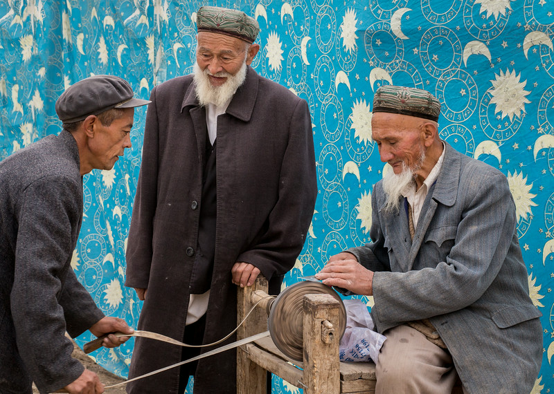 Opal Village, near Kashgar, China: sacrificing a sheep requires a sharp knife; on this day before the Kurban holiday, the customer on the left provides power to the grinding wheel as a knife is sharpened.