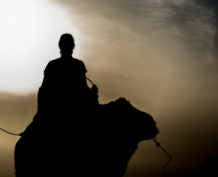 Flaming Mountains, near Turpan, China: a camel-mounted tourist is silhouetted against the setting sun.