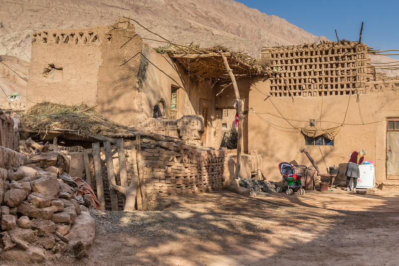 Tuyuk Village, Turpan, China: a traditional adobe mud house, but with a washer/dryer and modern baby stroller in the yard