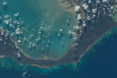 Caption by Space Station Academy student: This image shows the largest arm of the Acklins/ Crooked Islands, where is featured the Mason's Bay and  Snug Corner. Is also possible to observe the land, which is not so fertile and just hold big ponds (beige spots) with a great amount of salt. Thanks to the Easter look at the the islands, the view is able to show the Blue Holes (one of the biggest in the world, the Dean's Blue Hole), which are in dark blue in contrast with the beach water and also the reefs near the beach. Is important to let notice, the great sand banks that lie near the coast, which indicate how deep is the sea. Taking pictures of the Dean's Blue Hole and it's companions, allow scientists to keep track of the levels of erosion and melting of the ice caused by the global warming. The growth of the Blue Holes, depend on the sea level and climate conditions, so several pictures of blue holes can show the changes through the years. There's also the quality of the reefs, which most are in danger.