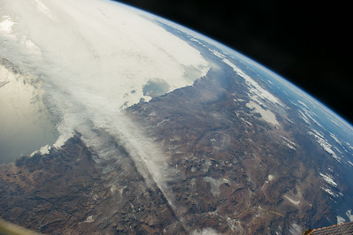 Caption by Space Station Academy students: 1) This is a picture of the snow-capped mountains in Western Argentina.  This can show a progression of more or less snow.  It could possibly show how fault movement brings the mountain higher. 2)  This image shows the Andes Mountains in northern Chile, Bolivia, and southern Peru. The clouds seem to hug the coastline then slice inland. Toward the upper right, the brown mountains become the green of the Amazon Basin.  The Andes have exceptional detail, folding and jutting along the western coast of South America. Midframe about two thirds of the way across, the beige patch is Salar de Uyuni, the worlds' largest salt flat.