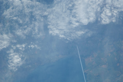 Caption by Space Station Academy student: This photo shows a jet above the Bristol Channel headed toward Swansea Bay and Swansea, United Kingdom.  The land to the east lies the beaches of Port Talbot, Wales. The land to the east looks like a quilted patchwork of colors, making me think of how it appears when flying over the midwestern United States in an airplane.  There is a lot of cloud cover and it looks as though the plane in this photo is about to encounter some turbulence.